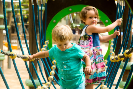 happy kids: Little sisters having fun at action-oriented playground