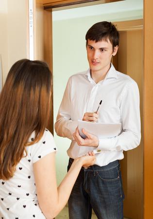 social worker: Young social worker questioning girl at door
