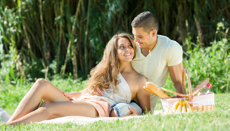 Happy young couple on picnic at summer day  photo