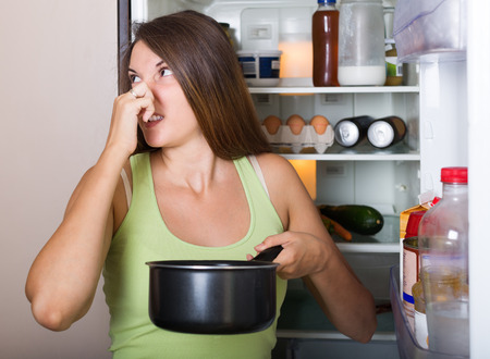 Young woman holding foul food near refrigerator at home photo