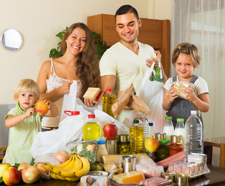 purchased: Happy parents with female children sorting purchased food out indoor