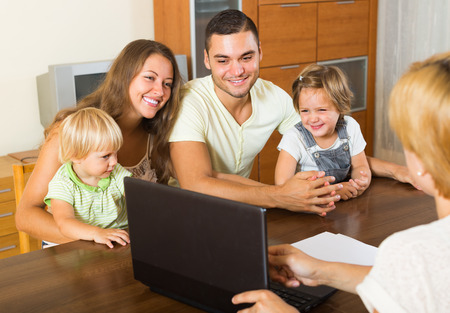 polls: Insurance agent consulting happy young family with kids indoor  Stock Photo