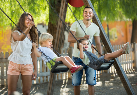 Young cheerful family of four at playgrounds swings. Focus on girl