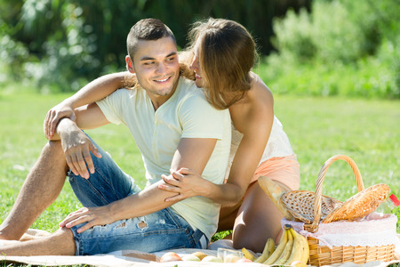Happy young romantic couple on grass in picnic at park in summer day  photo