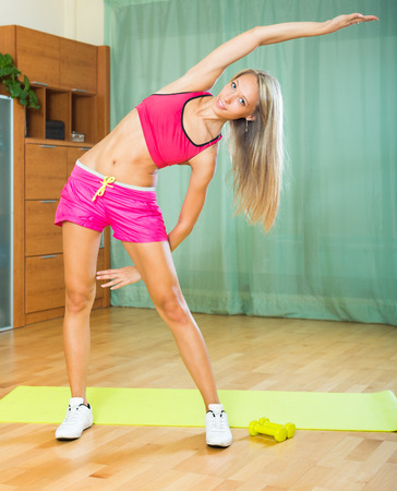 house trained: Smiling young female working out with dumbbells at home  Stock Photo