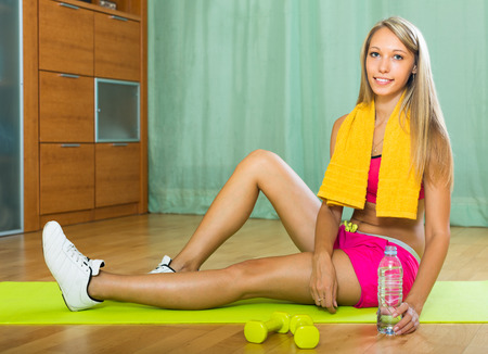 house trained: Active young woman with towel and bottle of water after training