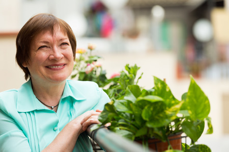 Happy senior woman sitting on balcony and smiling photo