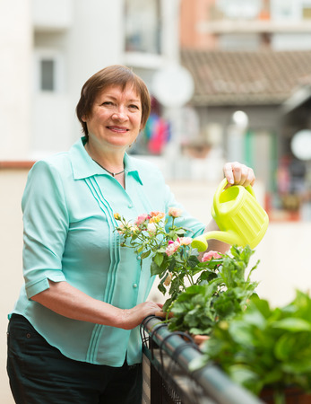Positive smiling senior woman watering decorative plants on balcony photo