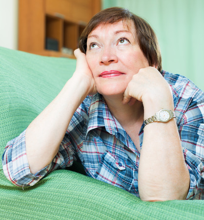Portrait of sad mature woman having tough time and laying on couch at home photo