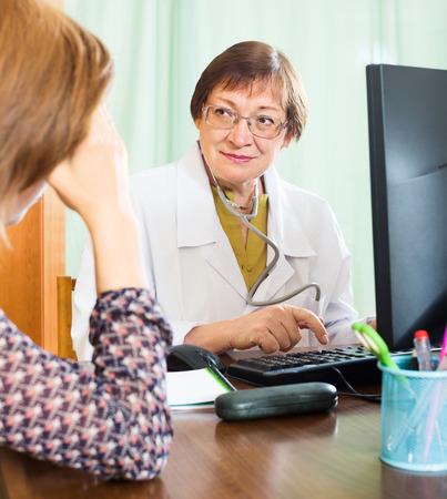 arzt gespr�ch: Weibliche Patienten mit medizinischen Beratung im B�ro von Oberarzt Lizenzfreie Bilder