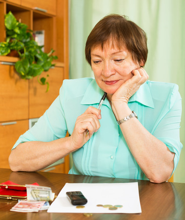 Pensive woman sitting at the table with money and bills photo