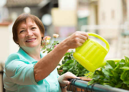 Smiling positive aged woman watering decorative flowers on balcony photo