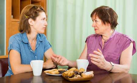 Mature woman talking with her young daughter and drinking coffee photo