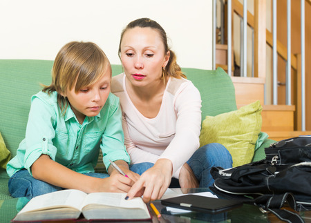 Mother with schoolboy son doing homework in living room  photo