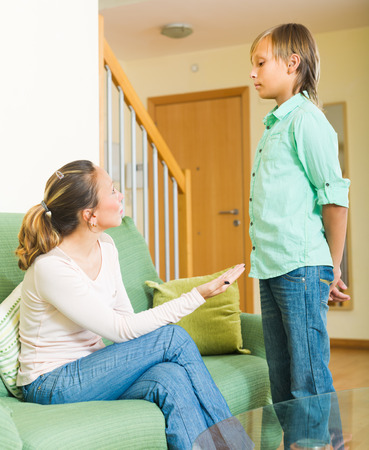 Adult mother scolding naughty teenage son in living room at home  photo