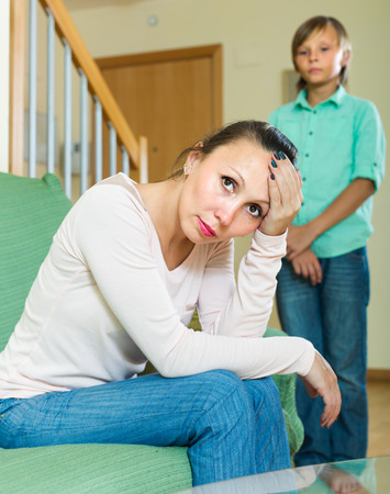 fracas: Mature mother sitting sad after quarrel with teenager son at home Stock Photo