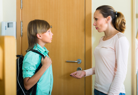 Positive mature mother lecturing boy before he goes to school