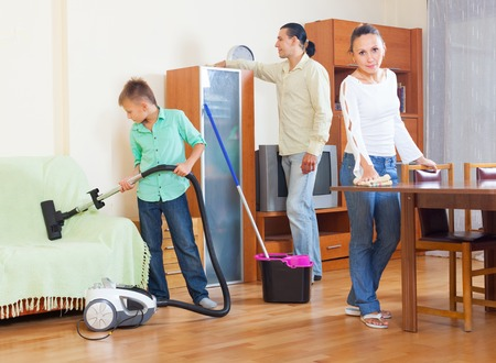 chores: Happy family of three cleaning with vacuum cleaner in home