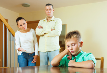 Parents berates her teenage child in interior. Focus on boy only