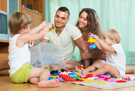 Smiling man with young wife and two daughters plays with meccano set in home  photo