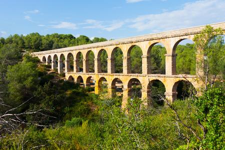 acueducto: Antique roman aqueduct in summer forest. Tarragona, Catalonia