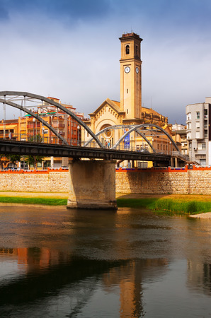 ebre: TORTOSA, SPAIN - AUGUST 12, 2014: Day view of Bridge called Pont de lEstat over Ebro river and church in Tortosa, Spain Editorial