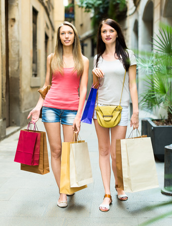 Two pretty young girls walking with shopping bags in European city photo