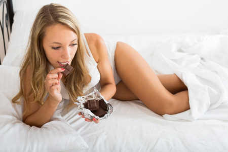 furtively: Girl eating chocolate in her bedroom in the morning
