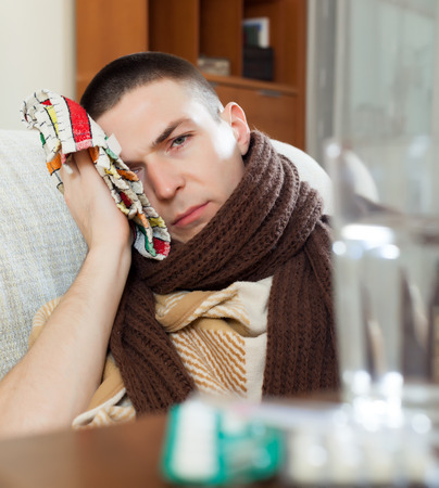 Suffering man in scarf  stuping  towel to head