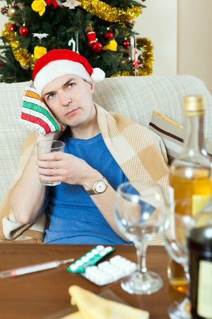 cephalgia: Young man in red New Year  hat  stuping  towel to head