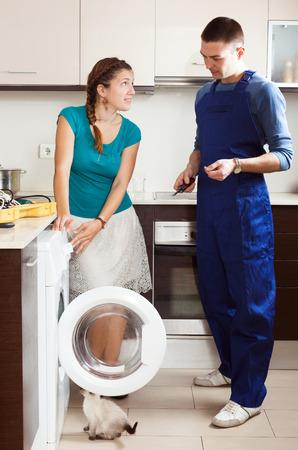 Housewife watching as engineer  repairing washing machine in a kitchen photo