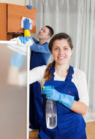 Man and young woman cleaning in living room photo