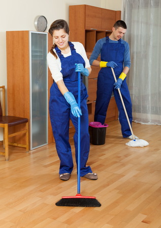 houseman: Handsome cleaners team working at living room