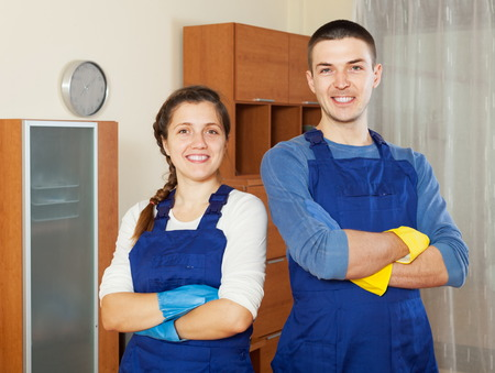 houseman: Smiling cleaners cleaning living room at home