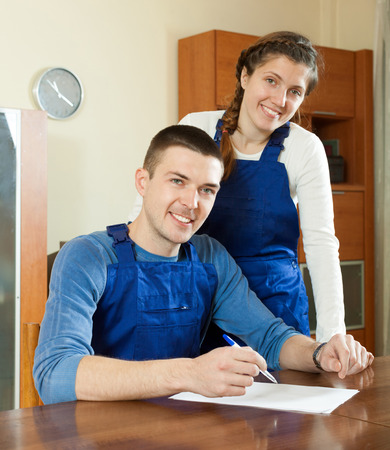 Happy workers in uniform with financial documents at table   photo