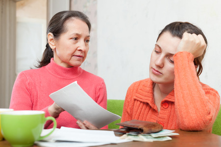 Mature mother scolds adult daughter for utility payments bills or credits. Focus on mature