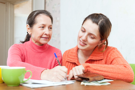utility payments: adult daughter helps the mother to fills in  utility payments bills Stock Photo