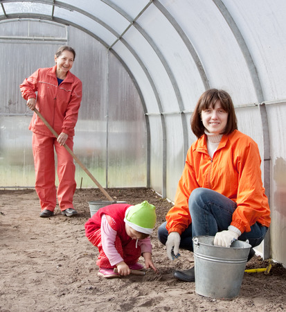 sows: Happy family sows seeds in soil at greenhouse Stock Photo