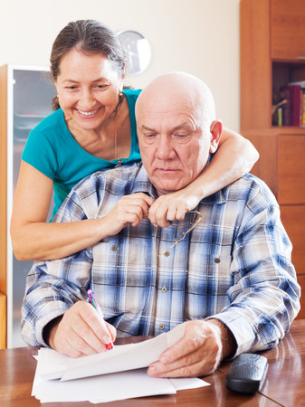 mature couple fills in paper documents together at photo