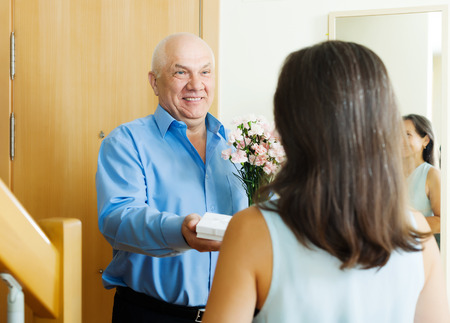 Smiling mature man giving jewel in box to woman at home door photo