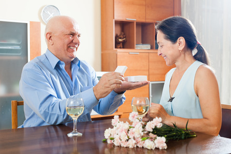 Mature man presenting woman jewel in box  at table photo