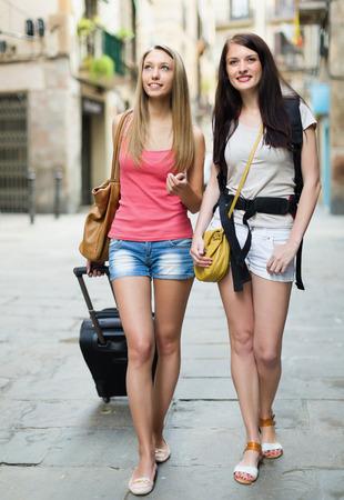 Two smiling women with luggage walking through city street photo
