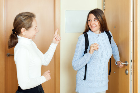 parting off: Mature woman sees off adult daughter at the door from home
