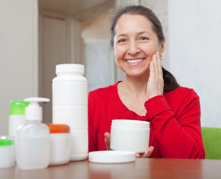 Happy mature woman puts cream on face at home interior photo