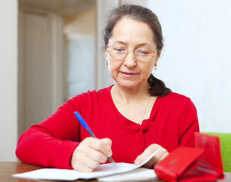 calculated: serious mature woman is calculated the family budget at  home