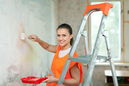 housepainter: Female house painter paints wall with brush