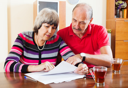 parsimony: serious mature couple reading financial document Stock Photo