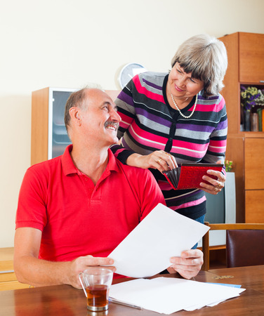 Positive mature couple looking financial documents in home interior photo