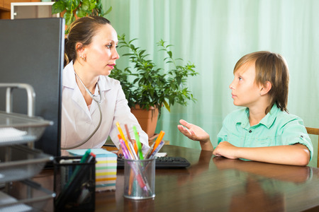 tells: Female doctor at the table listening to complaints boy patient Stock Photo