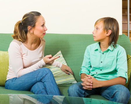 berate: Angry mother scolding teenage son in living room Stock Photo